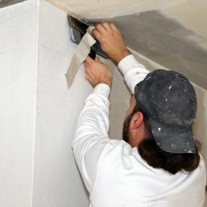 Handwerker (Maler) bei Tapezierarbeiten